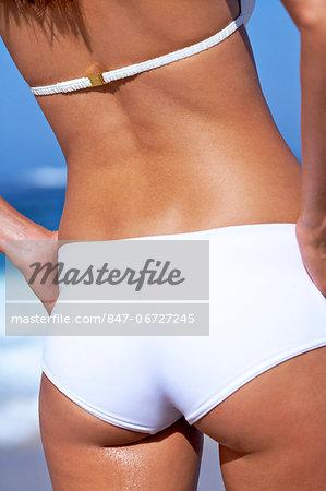 Beautiful woman with bare back and bikini bottoms on  beach