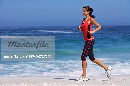 Beautiful brunette running on beach