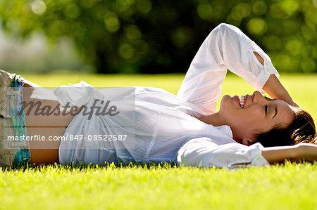 Beautiful brunette girl lying on the grass