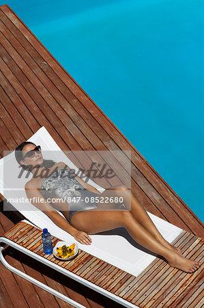 Beautiful brunette sunbathing on lounger