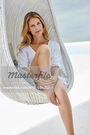 Beautiful woman sitting on swing chair outside