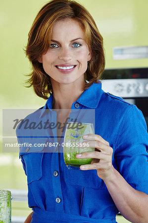 Beautiful woman enjoying a green smoothie.