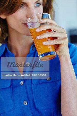 Woman enjoying an orange juice.