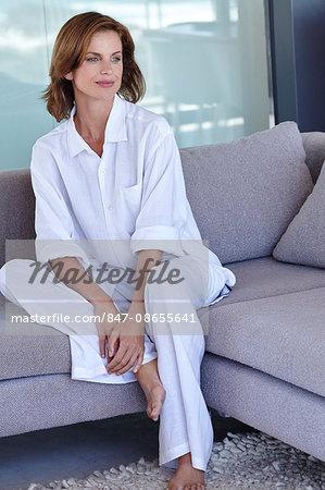 Beautiful mature woman relaxing in white linen.