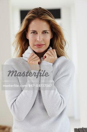 Portrait of beautiful blonde woman in white jumper