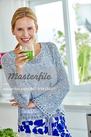 Healthy woman juicing green vegetables
