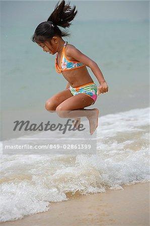 Girl jumping into sea