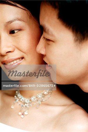 Man whispering into woman's ear