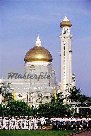 Brunei, Air force airmen march during Sultan Hassanal Bolkiah's birthday celebrations, Omar Ali Saifuddien mosque in background.