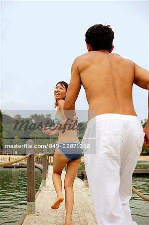 Man running after woman, rear view