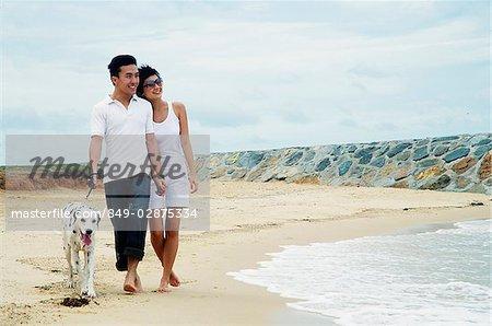 Couple walking on beach with Dalmatian