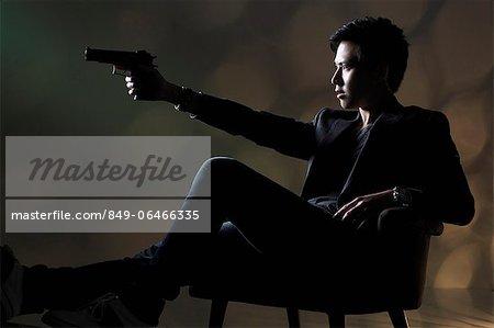 Young man sitting down pointing a gun