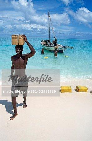 Man carrying box on head on beach,Vamizi Querimbas,Mozambique