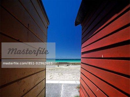 Looking between beach huts to Fish Hoek Bay,Cape peninsula,South Africa.