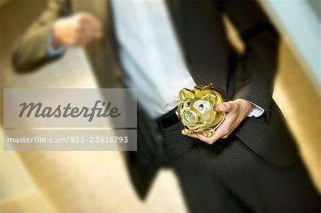 Man in front of safe deposit boxes holding golden piggy bank, close-up