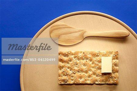 Sesame crispbread with butter on wooden board