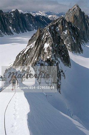 Mountaineer climbing on narrow ridge in Kichatna Mtns Denali National Park Interior Alaska Winter