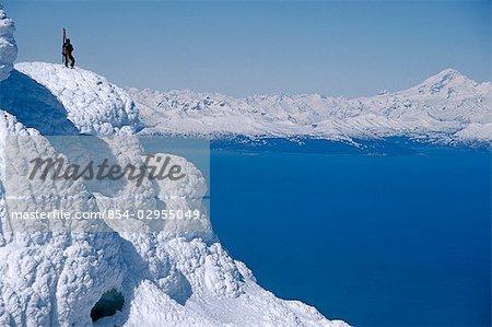Mountaineer Standing on ridge viewing vast scenery from Augustine Volcano across Cook Inlet Alaska