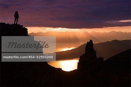 Female Hiker standing on peak overlooking Lynn Canal & Berner's Bay near Juneau Alaska at sunset