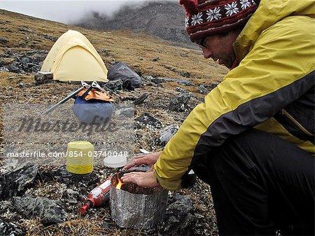 Backpacker prepares food at camp below Mt. Chamberlin, Brooks Range, ANWR, Arctic Alaska, Summer