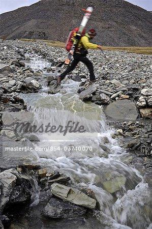 Backpacker crosses a creek in the Katak Creek valley returning from Mt. Chamberlin ski descent, Brooks Range, ANWR, Arctic Alaska, Summer