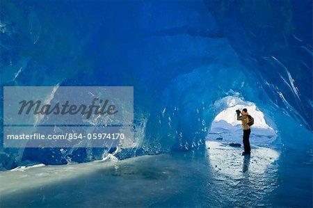 Man photographs inside an ice cave of an iceberg frozen in Mendenhall Lake, Juneau, Southeast Alaska, Winter