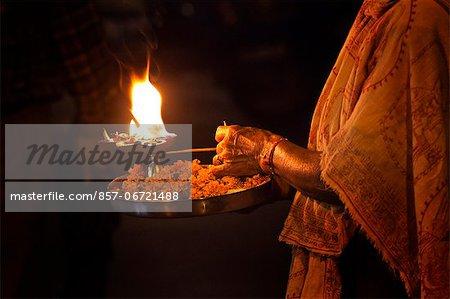 Priest holding a burning oil lamp in puja thaali during evening prayer (Aarti) at Har Ki Pauri, River Ganges, Haridwar, Uttarakhand, India