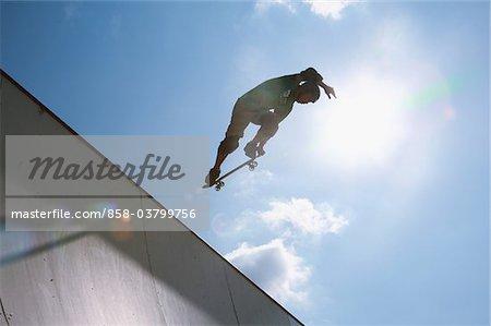 Skateboarder jumping from ramp