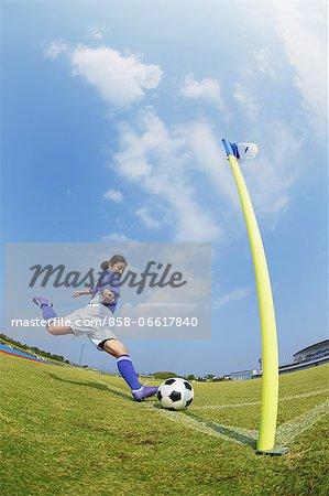 Woman In Soccer Uniform Kicking a Ball