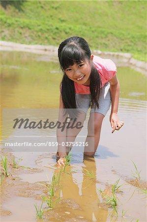 Girl Planting Seed At Wetland