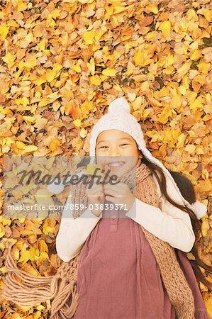 Preteen Girl Lying In Leaves