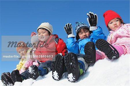 Children Sitting Together In Snow