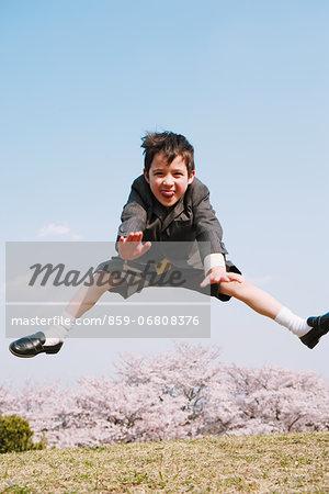 Young boy in a school uniform jumping