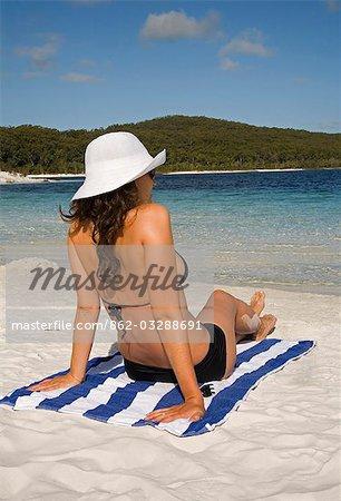 A sunbather sits back on the white sand beach of Lake McKenzie on Fraser Island.