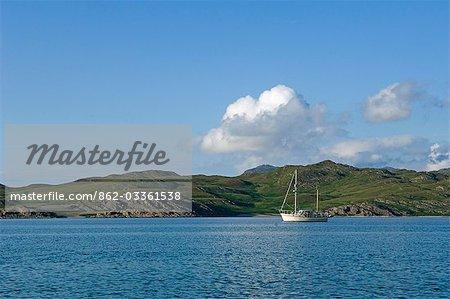A sailing boat quietly cruises along Loch Tarbert