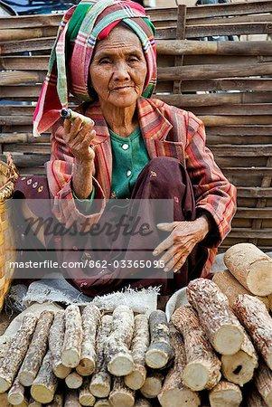 Myanmar. Burma. Nyaung U. An old woman smokes a local cheroot as she sells thanahka - the bark of Lemonira acidissimo tree ground to a paste with water for use as sunscreen.