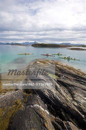 Norway,Nordland,Helgeland. Exploring Norway's coastal archipelago,a team of sea kayakers make thier way thorugh a string of islands.