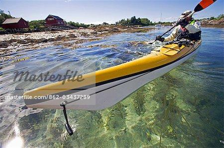 Norway,Nordland,Helgeland. Sea Kayaker explores the calm coastal waters of southern Nordland near the island of Rodoy