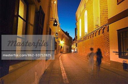 Lithuania, Vilnius, Two People Walking Along Stikliu Gatve At Dusk