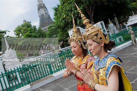 Girls in Thai dancing costumes in front of Wat Arun temple