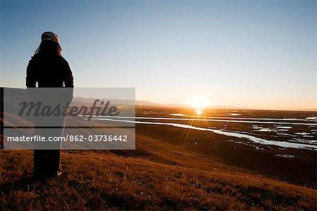China, Xinjiang Province, Bayanbulak, girl watching the sunset,
