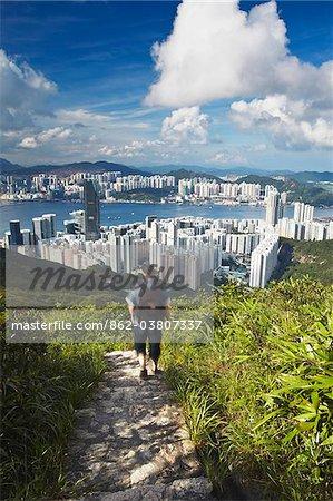 Man hiking on trail through hills behind Quarry Bay, Hong Kong, China