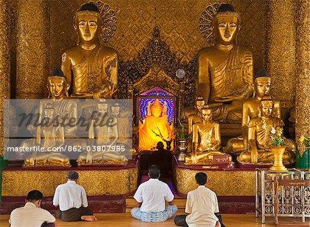 Myanmar, Burma, Yangon, Rangoon. Devout worshippers praying in front of golden Buddha statues, one with a halo of radiating electric light, at the Shwedagon Pagoda, Rangoon.