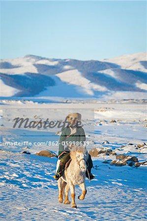Mongolia, Ovorkhangai, Orkkhon Valley. A man approaches on horseback at sunrise.