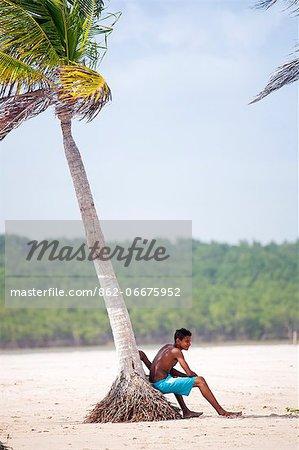 South America, Brazil, Para, Amazon, a local boy leans against a coconut palm on a river beach backed by Amazon rainforest near Soure on Marajo island