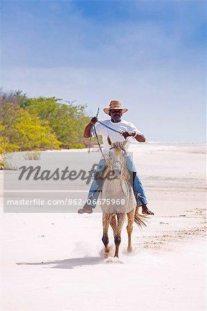 South America, Brazil, Para, Amazon, Marajo island, local man on horseback riding barefoot on the beach near Soure