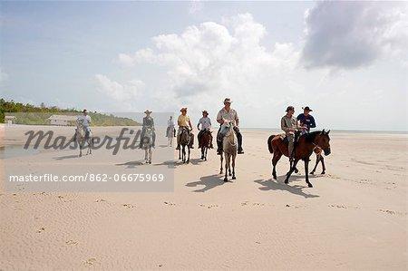 South America, Brazil, Para, Amazon, Marajo island, tourists on horseback riding on the beach near Soure