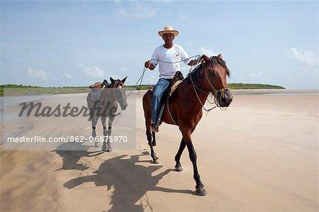South America, Brazil, Para, Amazon, Marajo island, local man on horseback riding on the beach near Soure
