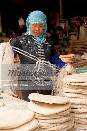 China, Yunnan, Jinghong. Sorting out noodles in Jinghong market.