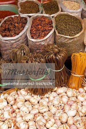 China, Yunnan, Jinghong. Spices garlic and rice noodles for sale at Jinghong market.
